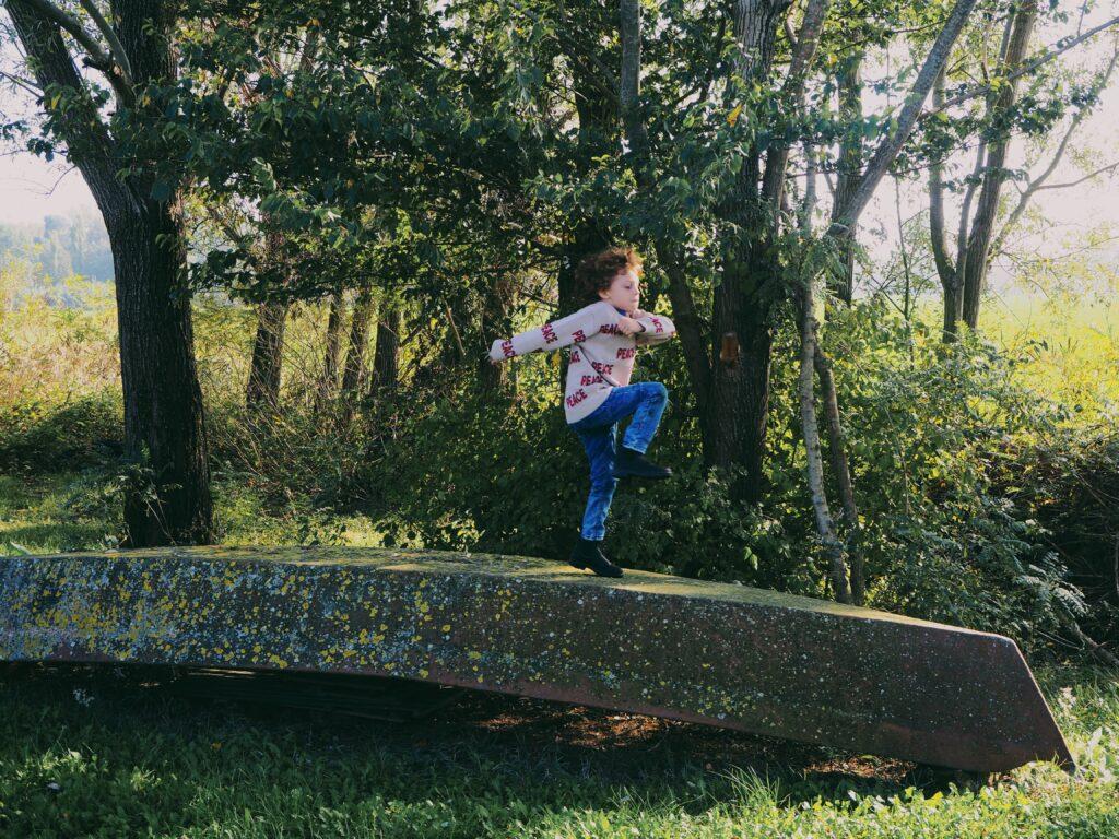 bambino che corre su barca rovesciata